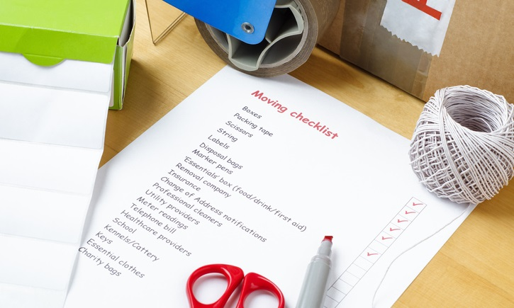 A moving day checklist on a desk with packing materials